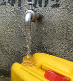 Yellow water canister with a running tap at a public standpipe. © GIZ