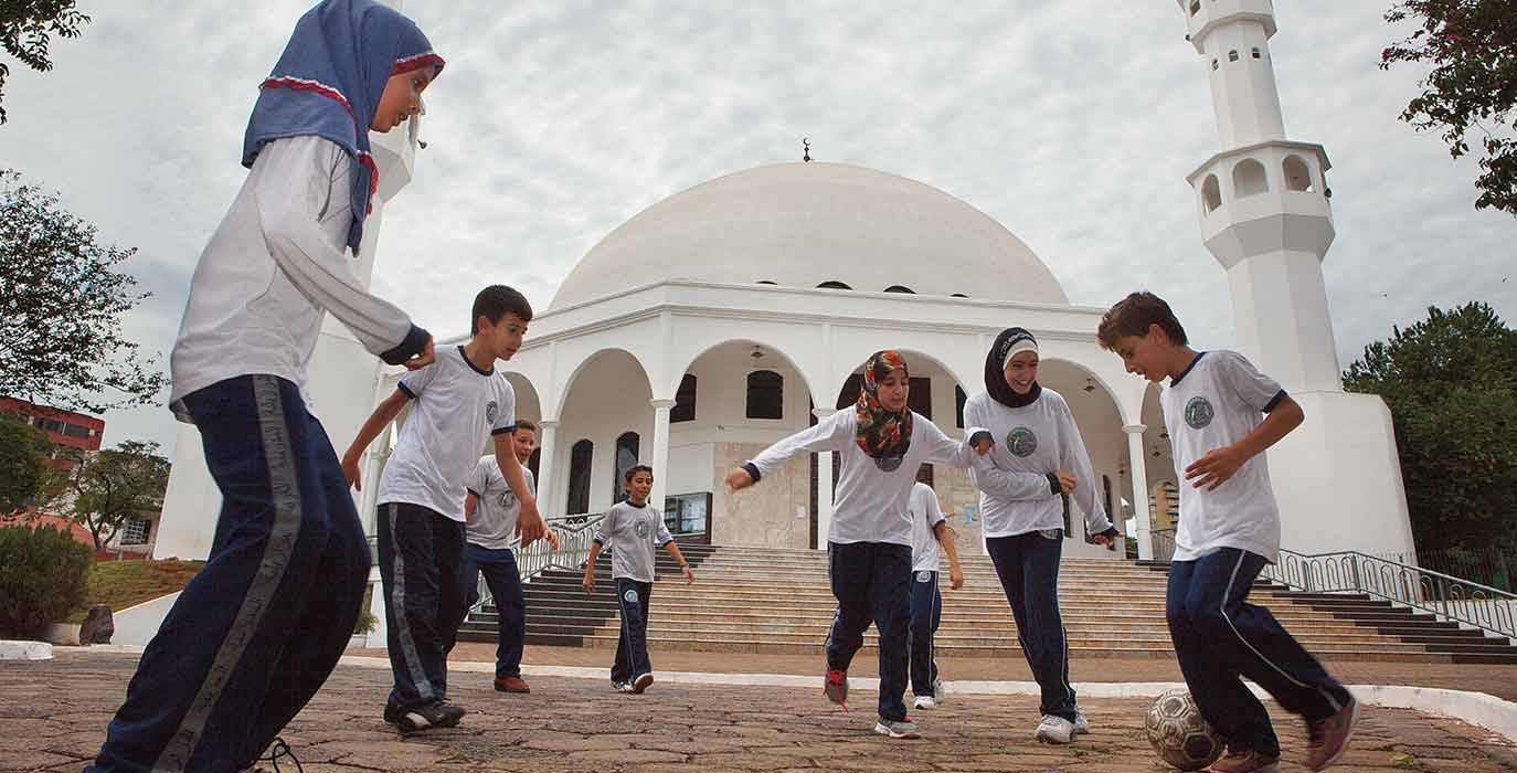Girls with headscarfs and boys playing football, mosque in background