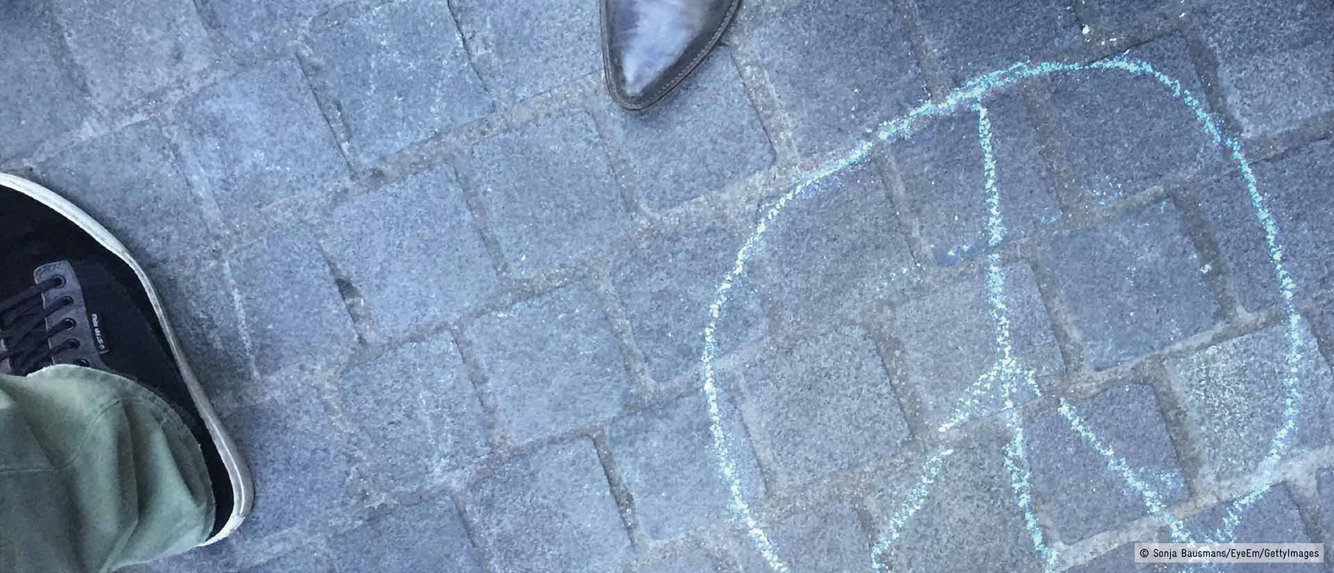 Low Section Of People Standing By Peace Symbol Drawing On Footpath