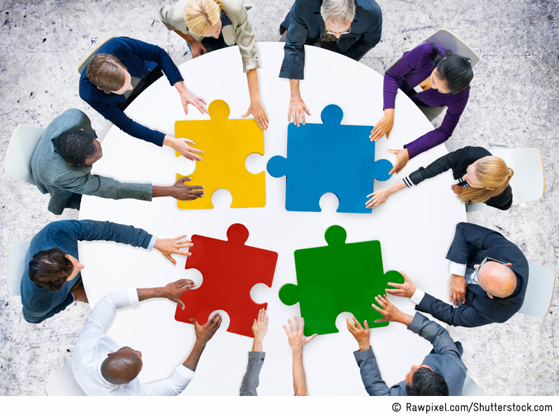 Bird's eye view of several persons sitting around a white table with four large puzzle pieces in primary colours